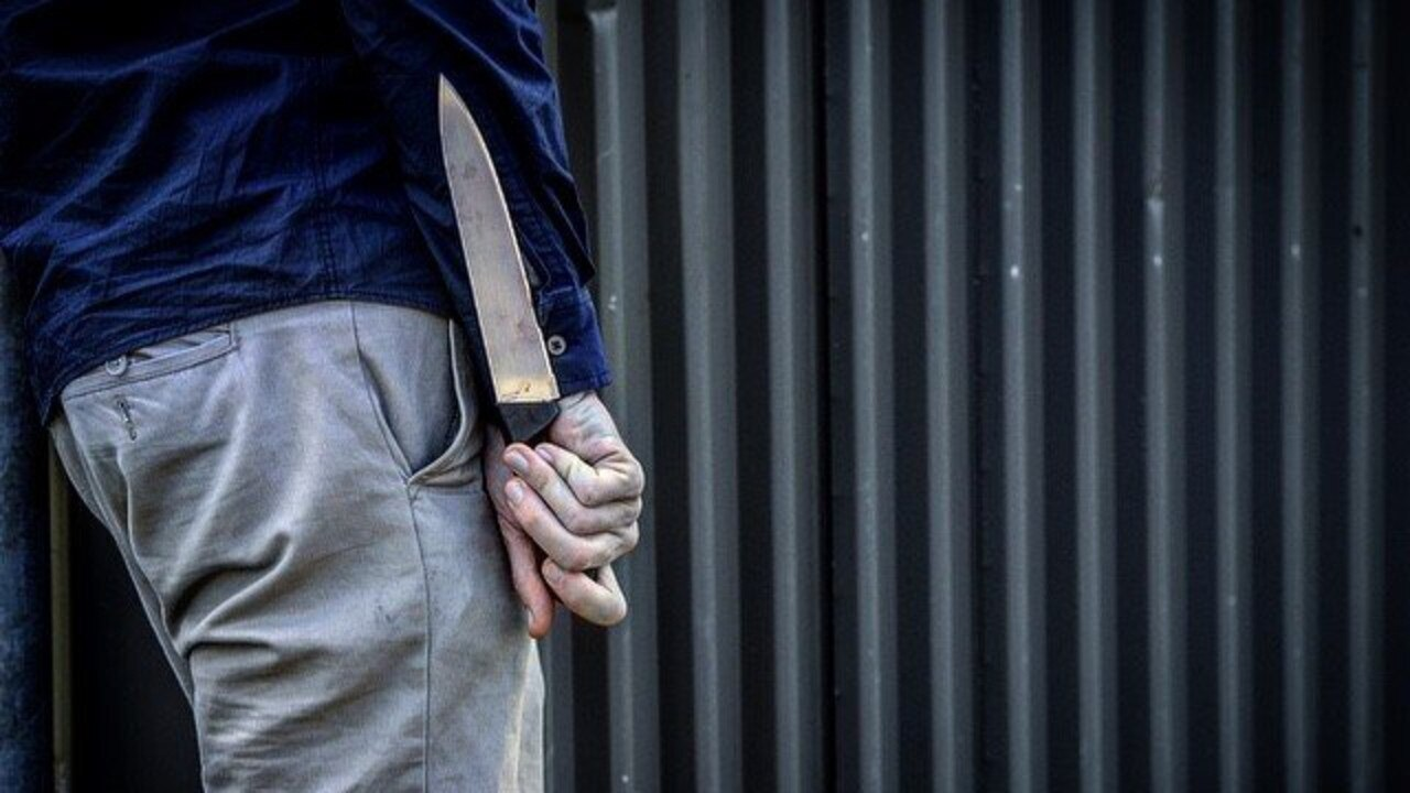 A person holding a knife. Photo: File.
