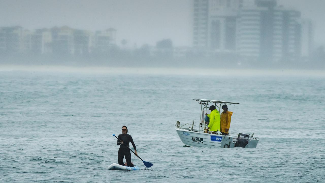 A paddle boarder and fishermen brave the rain at Mooloolaba Spit. Photo: Lachie Millard