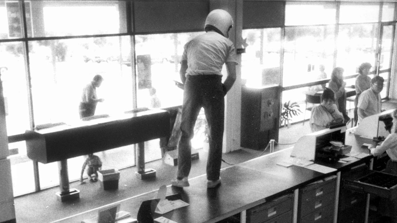 Still of security footage from an armed hold up at the NAB in Wynnum, September 1987. A man wearing a helmet and brandishing a pump-action shotgun jumps on the counter and demands money while a young boy cowers in fear under a table and customers freeze in their tracks.