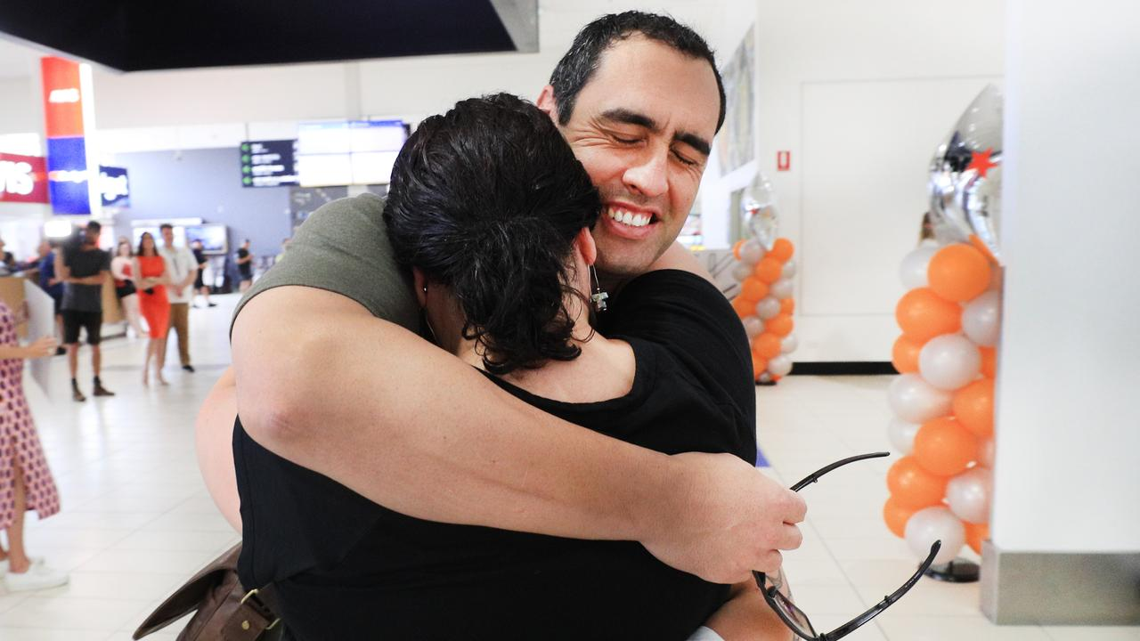 Yonni Paul bursts into tears after seeing his wife Carlina Paul for the first time in six months after he arrived in Queensland the first flight from Sydney. Picture: Scott Powick / News Corp
