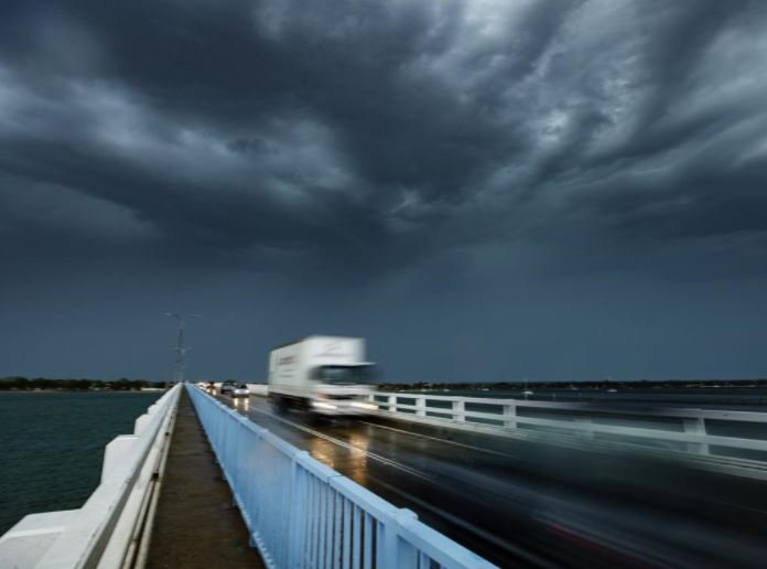 A storm cell passes over the bridge to Bribe Island as wild weather lashes southeast Queensland. Picture: Lachie Millard