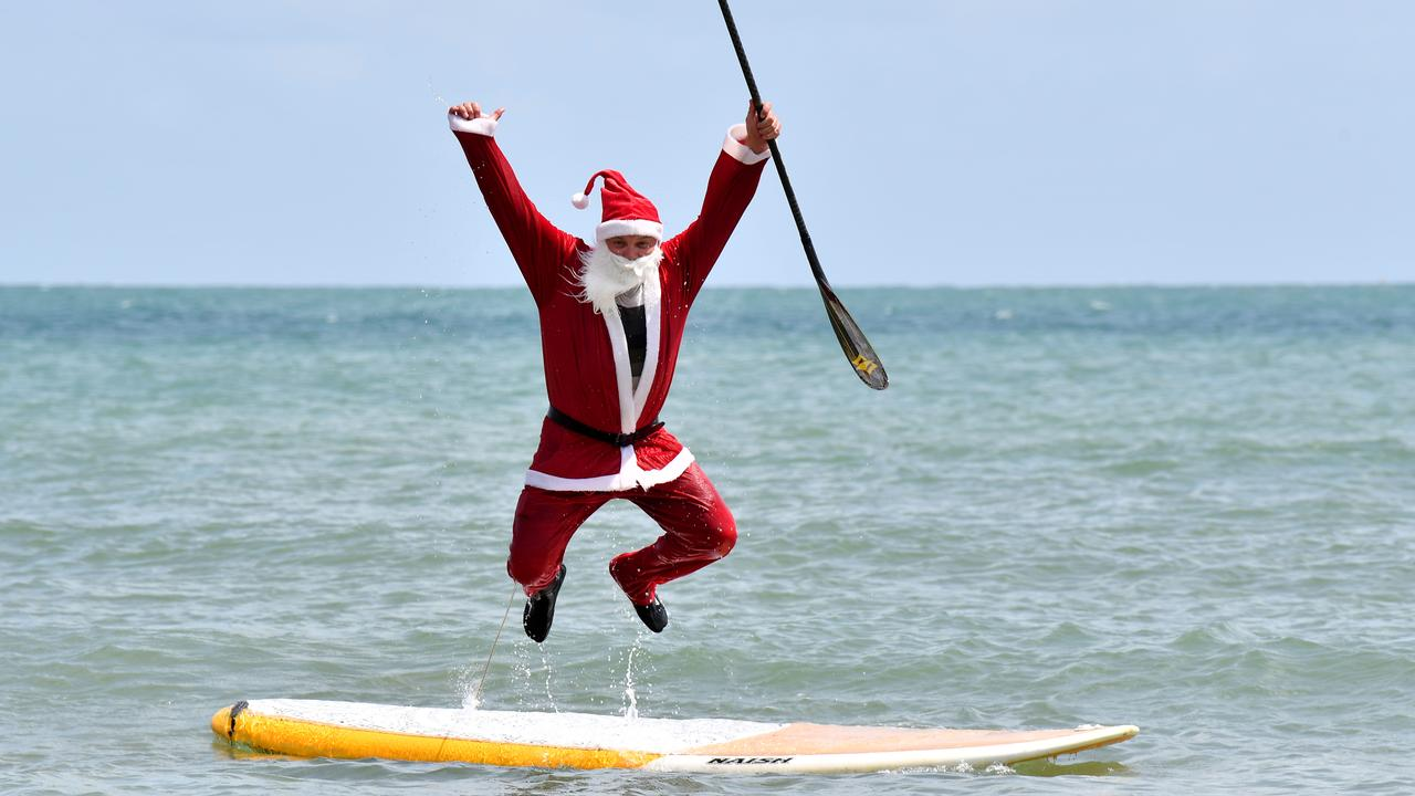 Santa (Ross Gee) has a dip at Eimeo Beach before Christmas, 2019. Picture: Tony Martin