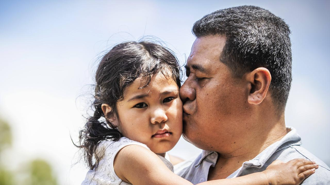 Three-year-old Faith Leiataua being comforted by her dad, Peniamina. Picture: Nigel Hallett