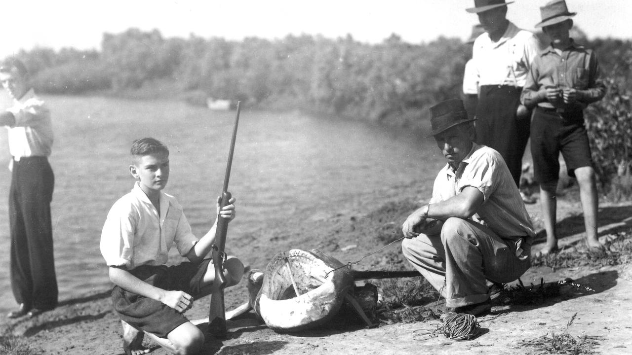 MONSTER CAUGHT: Jim Hamilton, with his rifle, and others with the shark that was hooked after Frank Gurran was mauled in Dump Creek in December 1939.