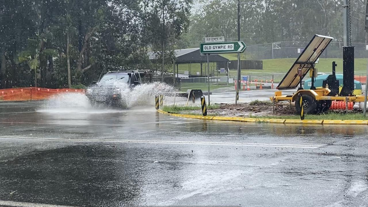 Motorists driving through the rain at the corner of Old Gympie Rd and Kilcoy Beerwah Rd. Photo: Natalie Wynne