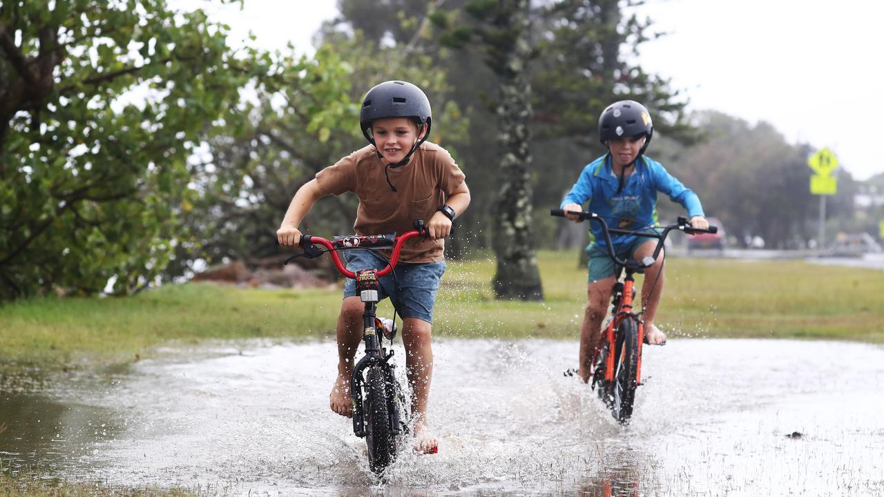 Baya Thorley and Harry Skews having fun riding their bikes while on holidays at Fingal as extreme weather lashes the North Coast of NSW. Picture: Jason O'Brien