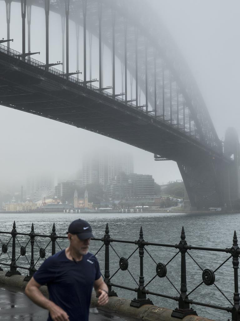 A runner pictured at Dawes Point with the Sydney Harbour Bridge cloaked in fog this morning. Picture: NCA NewsWire / Damian Shaw