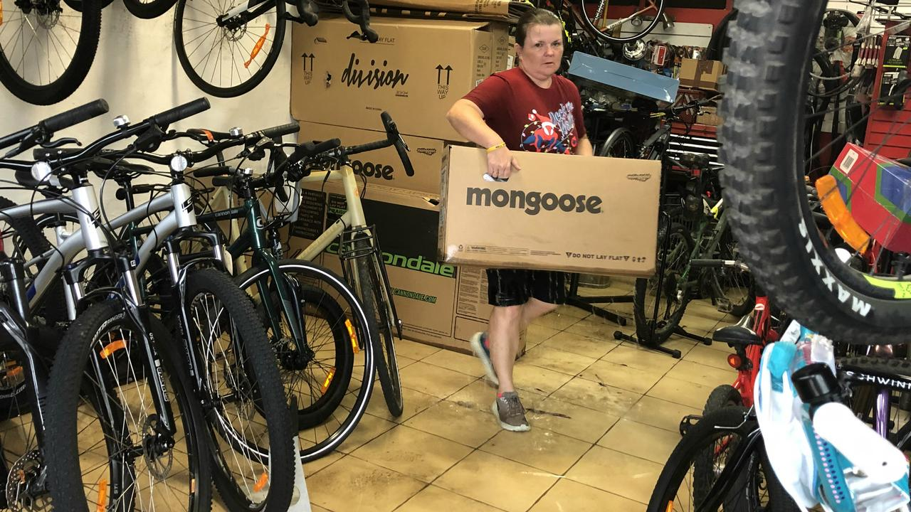FLASH FLOOD: Just Ride Cycles co-owner Rachel Sipple crries a bike away from the flood water at her Wyrallah Rd, East Lismore store. Photo: Alison Paterson