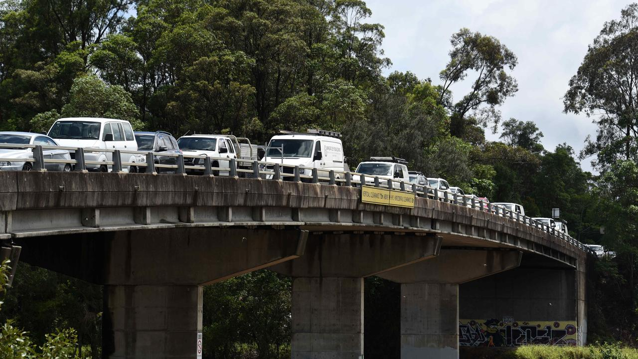 Locals at Tumbulgum park their cars on high ground on the bridge as flooding and wild weather battered the region this week. Picture: NCA NewsWire / Steve Holland