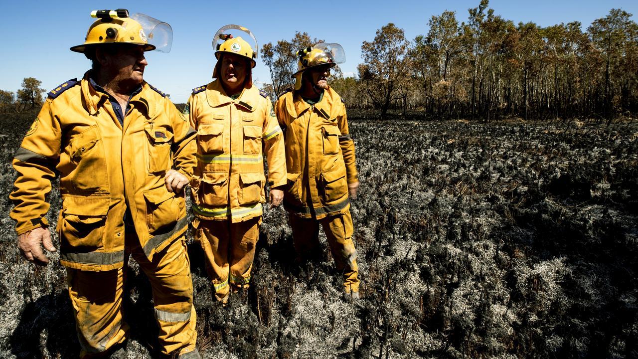 Rural Fire Service Firefighters Peter Garrett, Mark Smith, and Scott Brooks return to the ashes at Peregian Beach where they fought a fierce battle against a raging bushfire. Photo: Lachie Millard