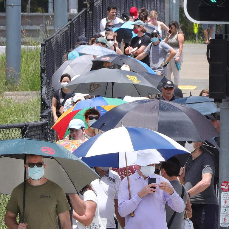 People using umbrellas to protect themselves from the harsh sun while waiting for hours. Picture Glenn Hampson