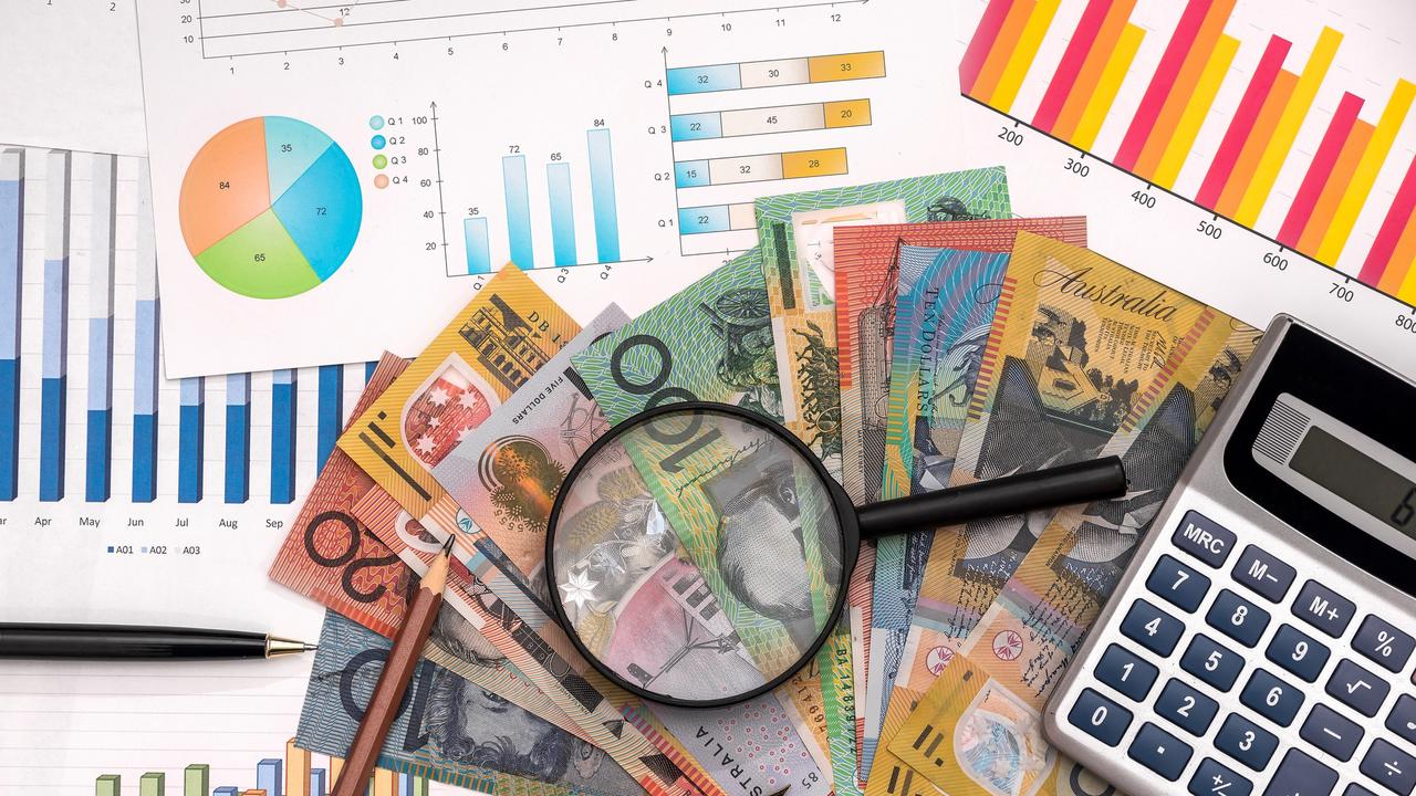 Business graphs with australian dollars, magnifier, pen and calculator