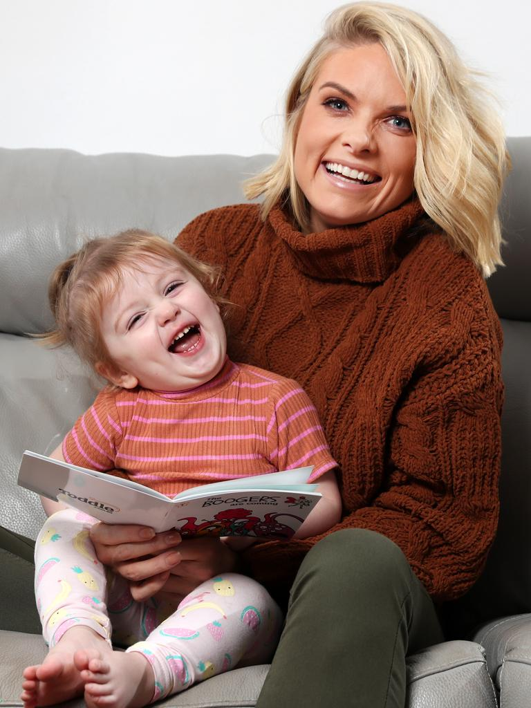 Erin Molan reading a book with her daughter Eliza. Picture: Jonathan Ng