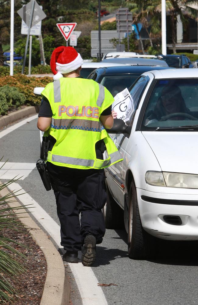 A Queensland police officer wearing a santa hat inspects the paperwork of people attempting to cross the Queensland border from NSW. Picture: Mike Batterham
