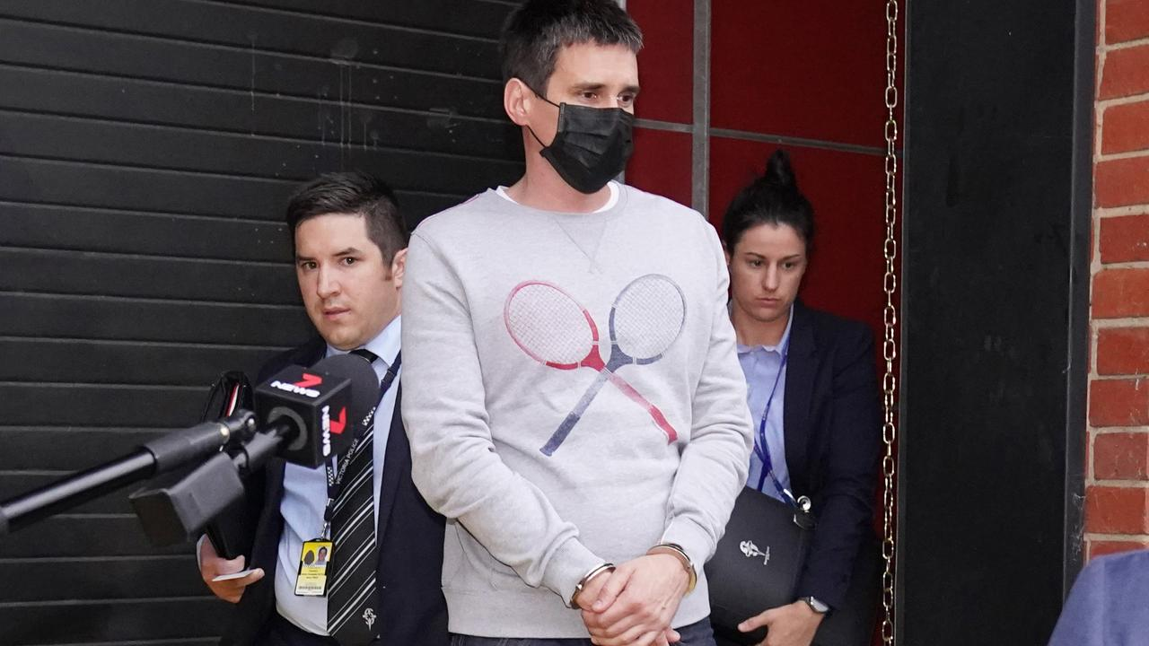 Richard Pusey is escorted from his home by detectives after the Eastern Freeway crash. Picture: AAP/Michael Dodge