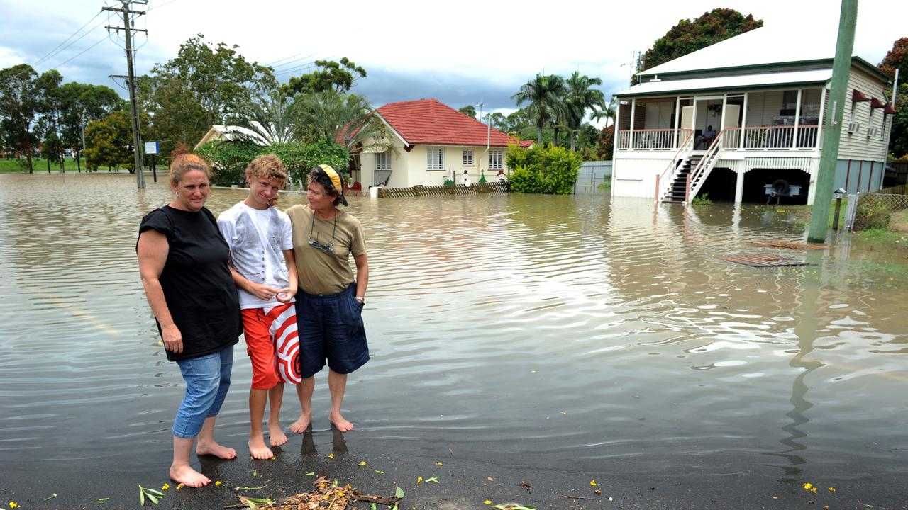 Kim Nilsen, David Nilsen and Ms Jipzy outside Kim's partially flooded home with the red roof in Maryborough Street. Photo: Mike Knott/NewsMail