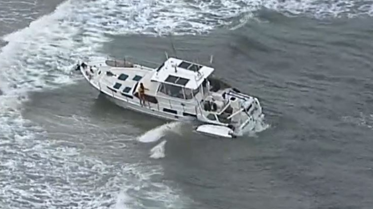 A police officer and lifesaver take control of the vessel. Picture: 7 News