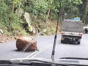 Huge boulder smashes in front of car