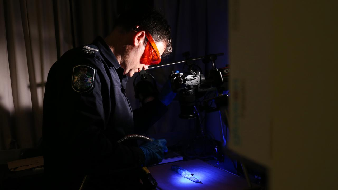Cairns police scenes of crime officer Wayne Boniface analyses a large knife under short wavelength light, set up for a simulated stabbing crime scene training exercise. Picture: Brendan Radke
