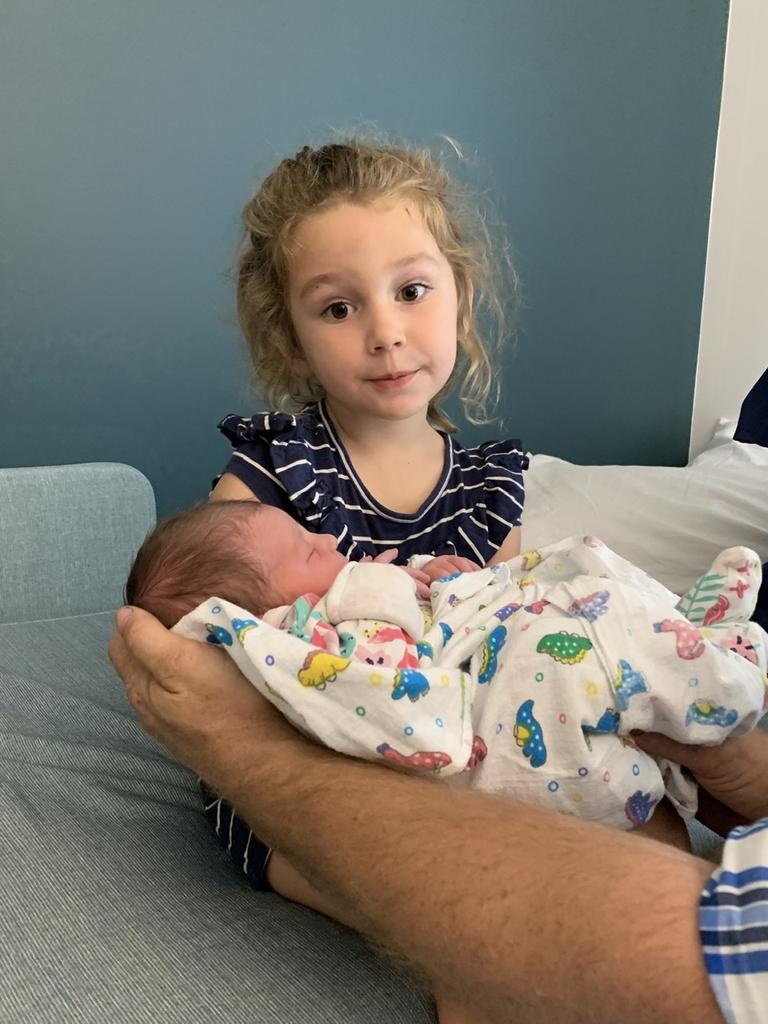 Cheeky Emily Elloy nursing her newborn sister Jessica. Pic: Lachlan Berlin