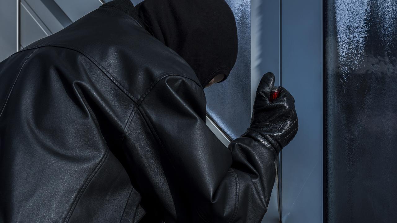 burgler with screwdriver at front door
