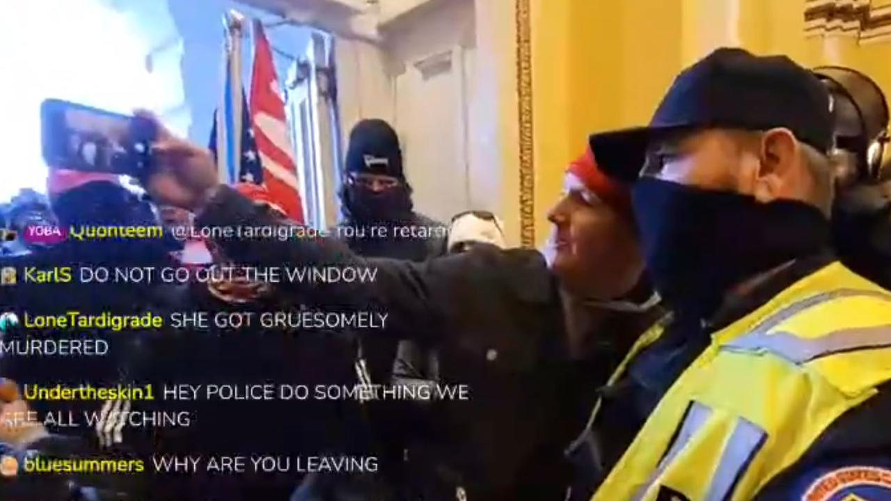 A US Capitol building police officer poses for a selfie with one of the insurrectionists who helped storm the US Capitol building.