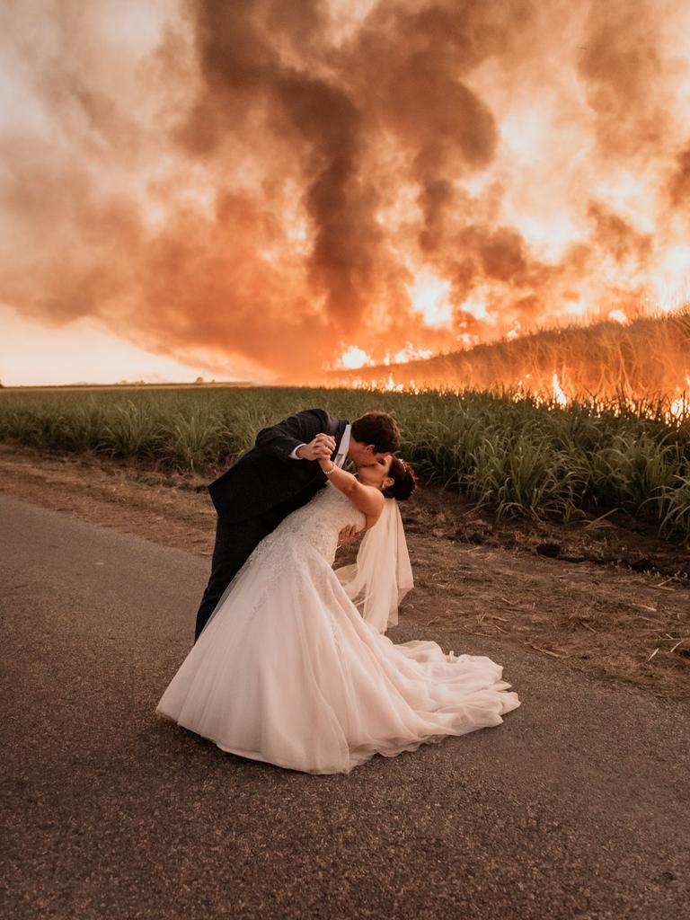 Travis and Ashlee Butler kiss in front of a burning cane field near Ayr. Photo: Rolling Portraits Photography