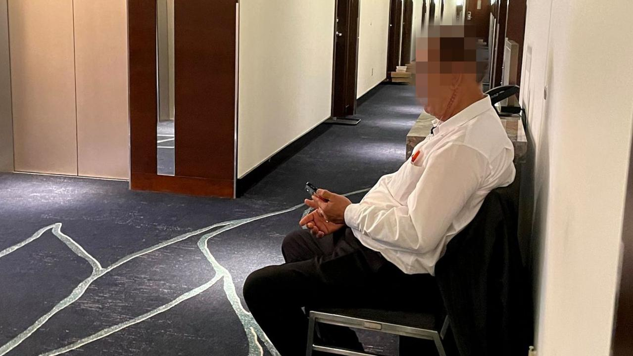 A maskless security guard outside a quarantined family's door at Intercontinental this week.