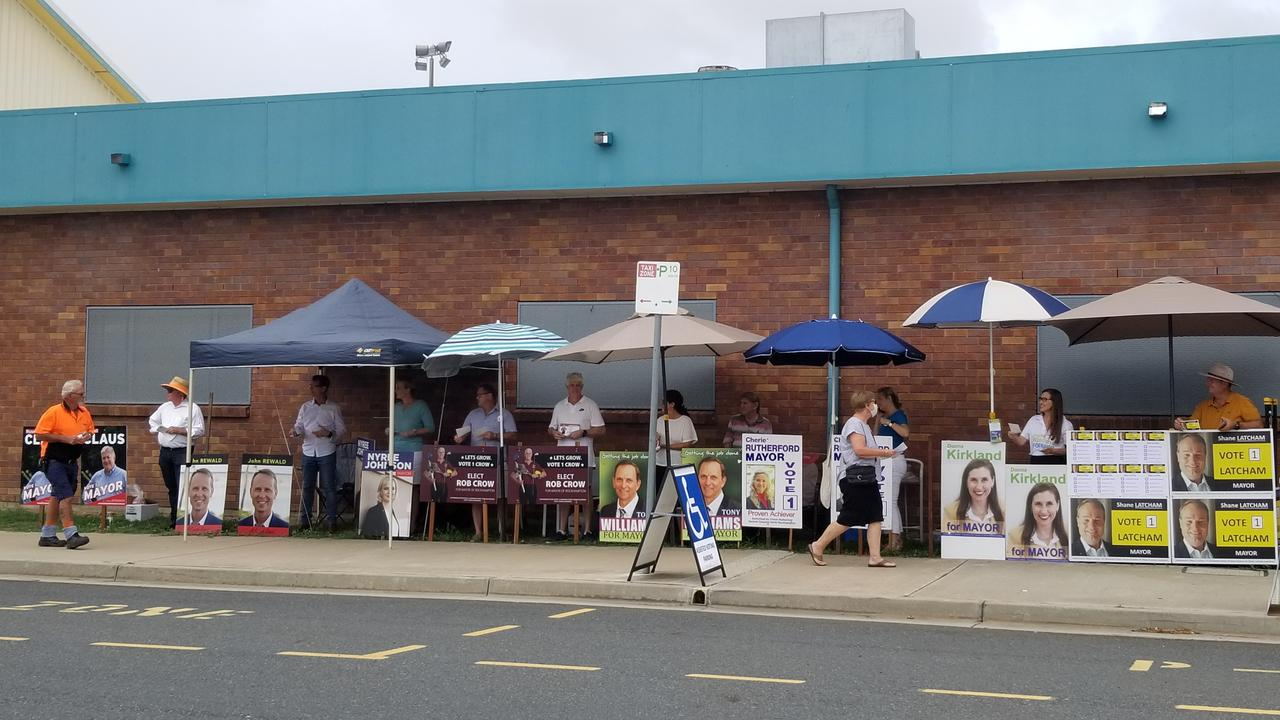 Candidates stationed outside the showgrounds hand out flyers.