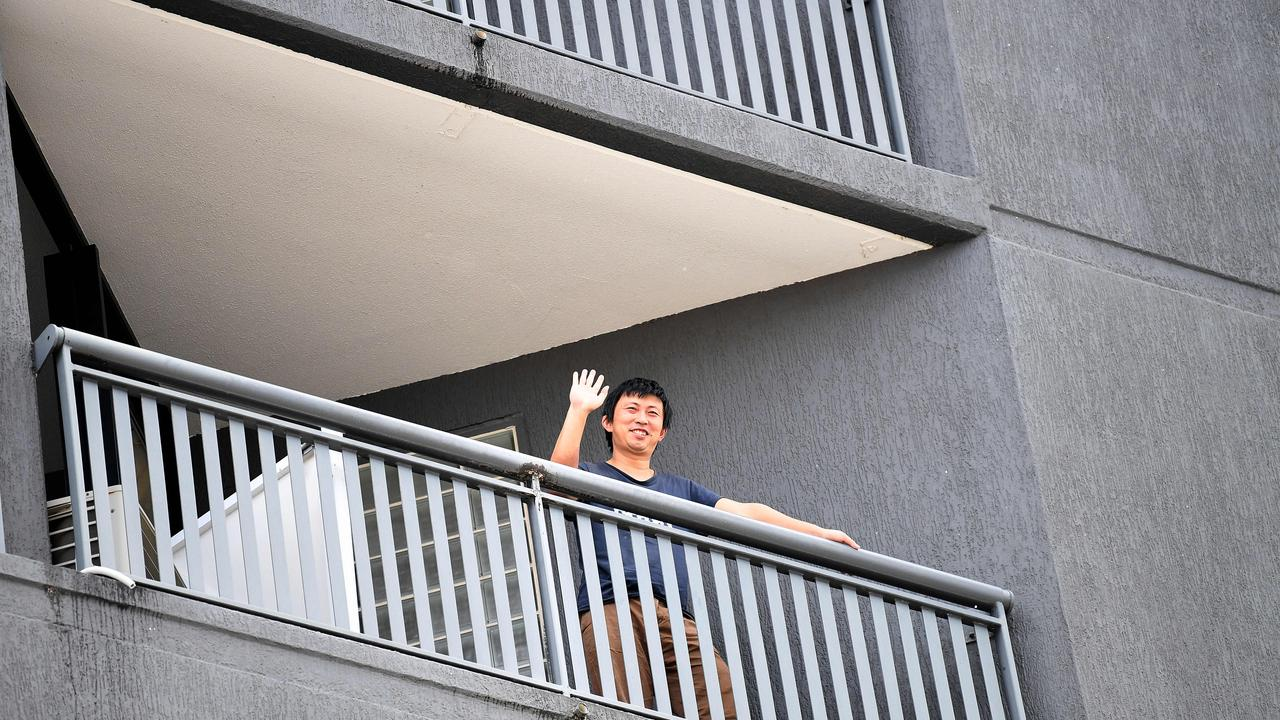 A quarantined guest waves from his balcony at the Hotel Grand Chancellor in Spring Hill, Brisbane. Picture: NCA NewsWire / Dan Peled