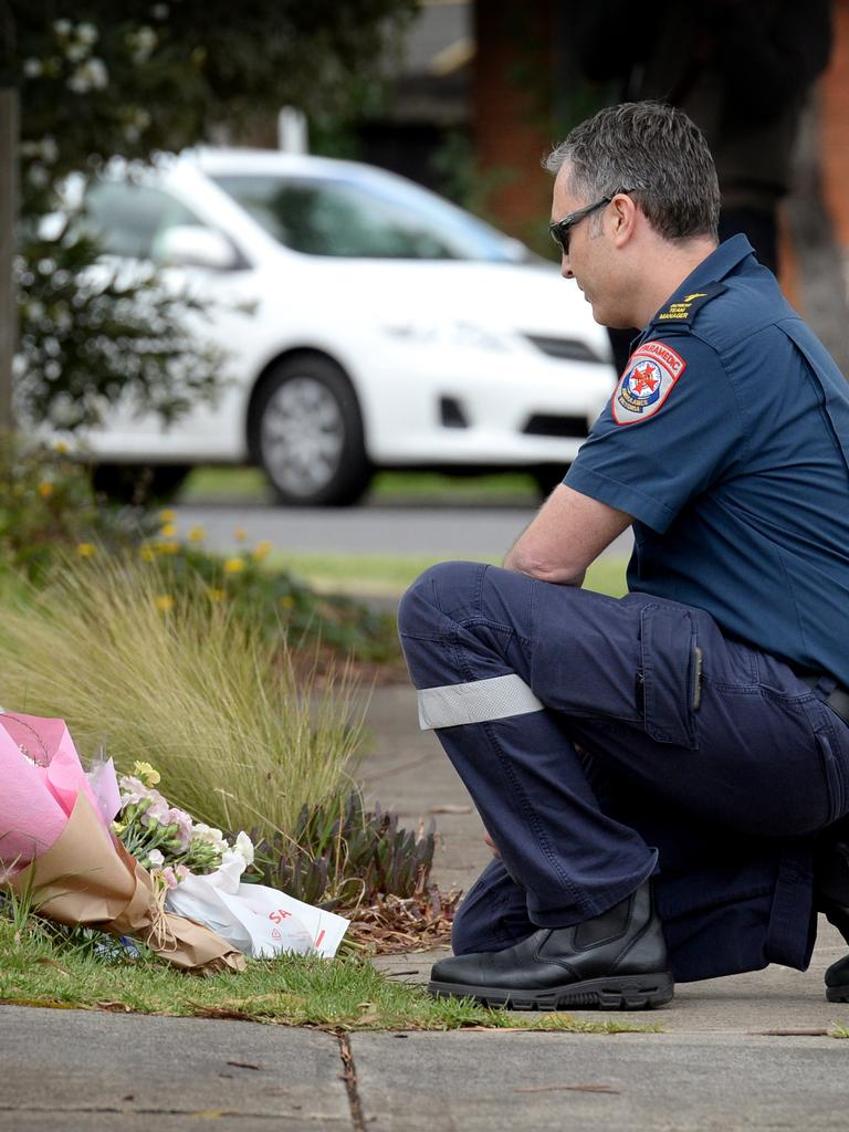 Lee, a paramedic, lays a floral tribute on behalf of the team at Ambulance Victoria's Westmeadows station Picture: Andrew Henshaw