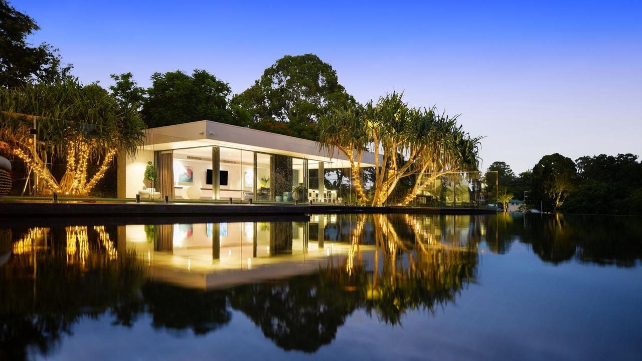 An infinity pool runs between the house and the pavilion.