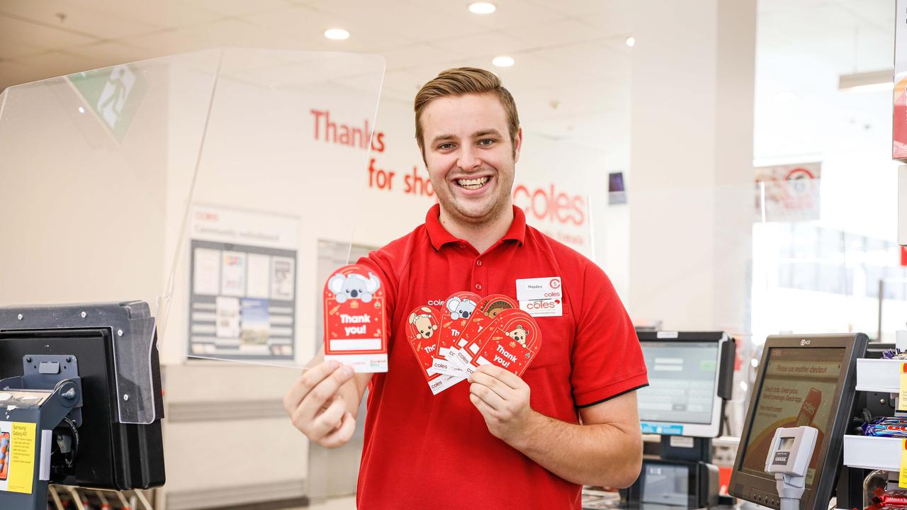 Coles team member Hayden Allen with Coles Christmas donation cards for SecondBite and Redkite.