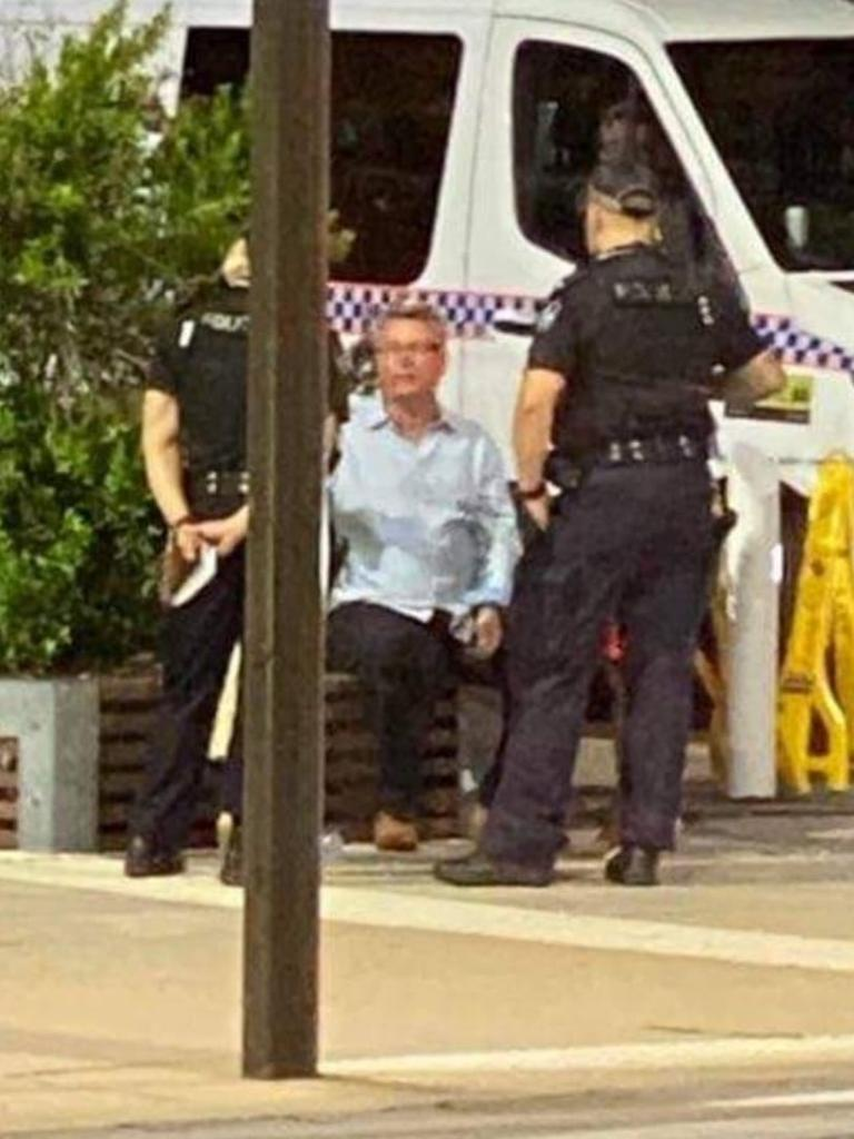 Les Walker sits with police officers at Flinders St on Saturday morning after being knocked out.