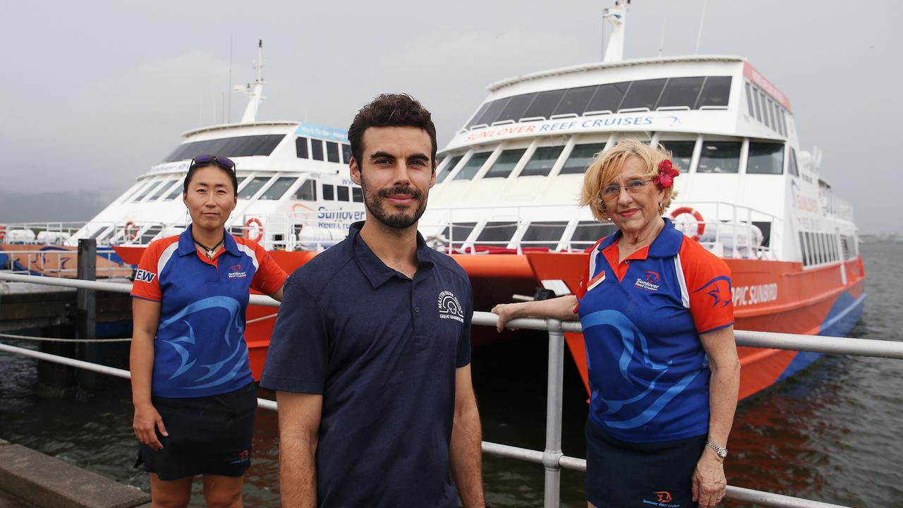 Tourism businesses like Sunlover Cruises are concerned what will happen to workers like dive instructor Ken Cho, photographer Pablo Cogollos and cruise attendant Nikki Lowmass once the payments cease. Picture: Brendan Radke