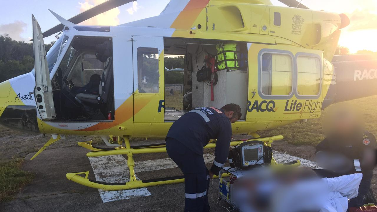 Crews from the Bundaberg RACQ LifeFlight Rescue helicopter assist patient on Fraser Island.