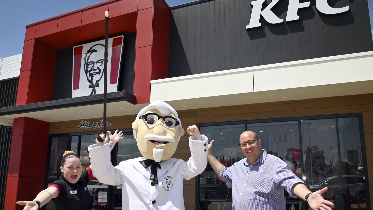 KFC opens in Highfields. KFC mascot, Colonel Sanders, with store manager Amber Harding-Dolan and area manager Trent Brigginshaw.