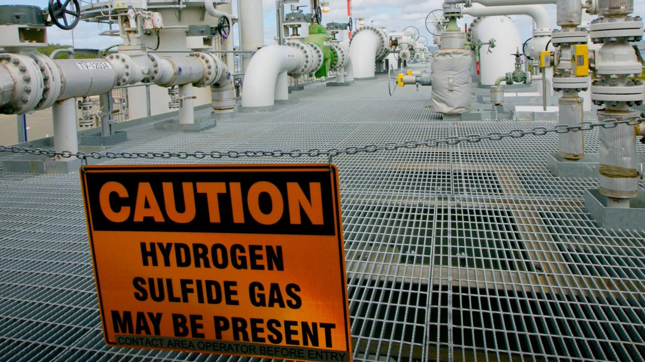 A sign warning of the presence of hydrogen sulfide gas hangs across a walkway at the Queensland Curtis Liquefied Natural Gas project site. Picture: Patrick Hamilton