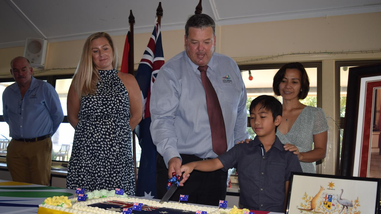 Mayor Andrew Willcox (centre) cuts the cake with new Australian citizens (from left) Hannah Griffiths and John, 10, and Venus Bishop at the Australia Day Citizenship Ceremony in Bowen. Photo: Elyse Wurm