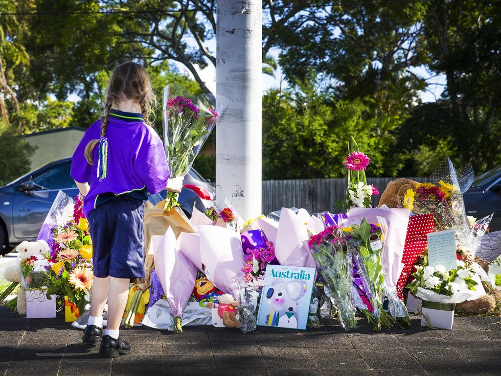 A child looks at the growing floral tributes at the scene of the tragedy. Picture: Nigel Hallett