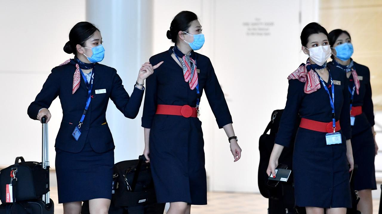 China Eastern Airlines cabin crew are seen wearing protective face masks at Brisbane International Airport on the day a public health emergency was declared in the state. Picture: AAP Image/Darren England