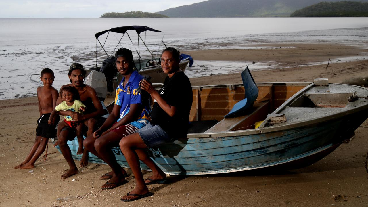 Relatives and friends Nulsa Neal, 8, Gary Neal, 1, Bradley Yeatman, Clive Sands, 18, and Tennelle Yeatman keeping a vigil on Yarrabah Beach. Picture: Stewart McLean