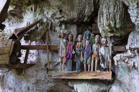 Row of dressed wood statues (called tau tau in local language) on a balcony inside the fascinating cave of the traditional burial site at Tampangallo, Tana Toraja, South Sulawesi, Indonesia.