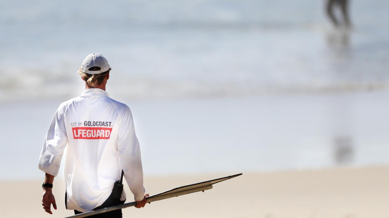 Gold Coast City Council Life Guards instruct swimmers to leave the water due to dangerous surf. Photo: Scott Powick NEWSCORP