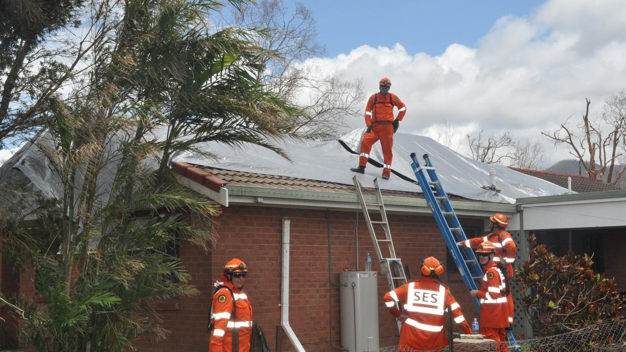 SES workers tarp a roof in Cardwell on Thursday after Cyclone Yasi.