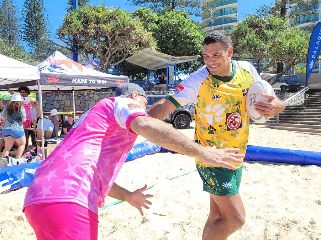 Former Wallabies flanker George Smith rounds up ex-Maroon Justin Hodges at the inaugural Beach Rugby competition at Mooloolaba. Picture: Matty Holdsworth