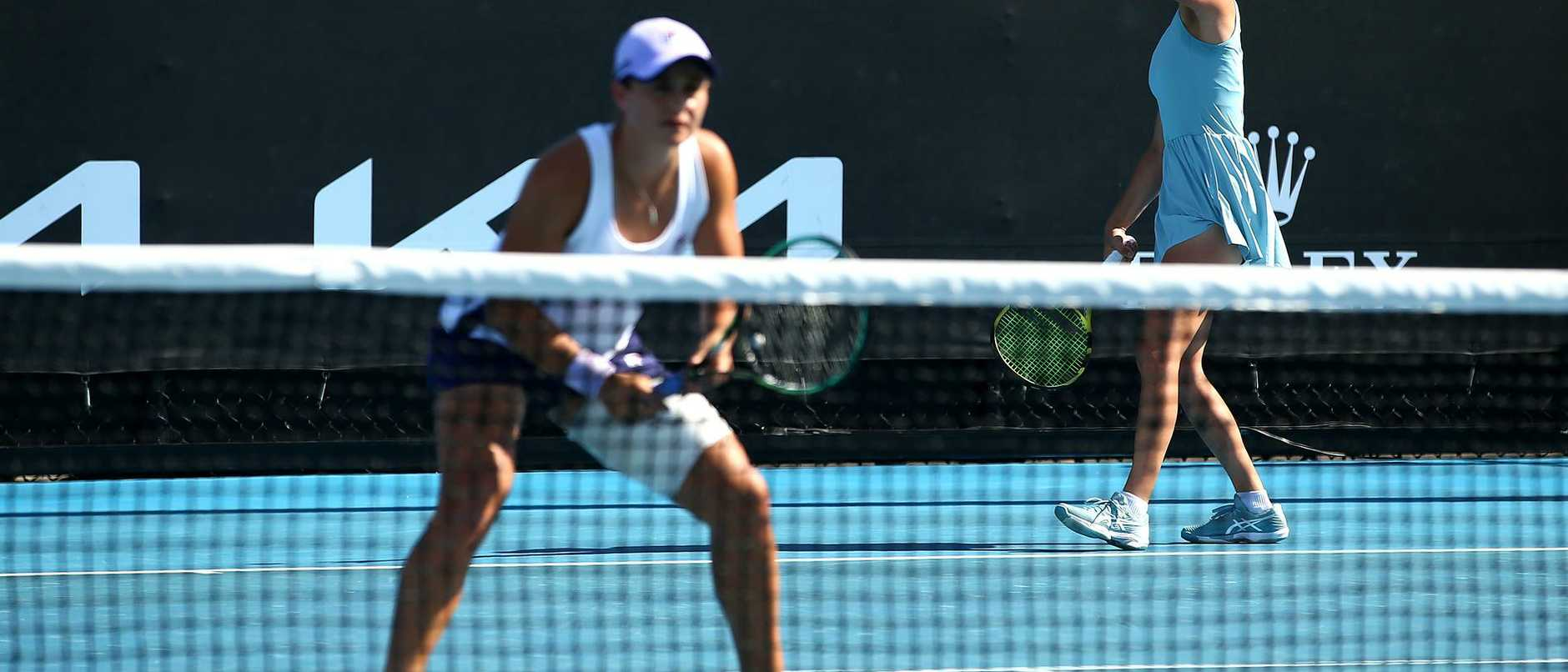 Ash Barty has taken to the courts with a heavily strapped thigh for a doubles match at the Australian Open
