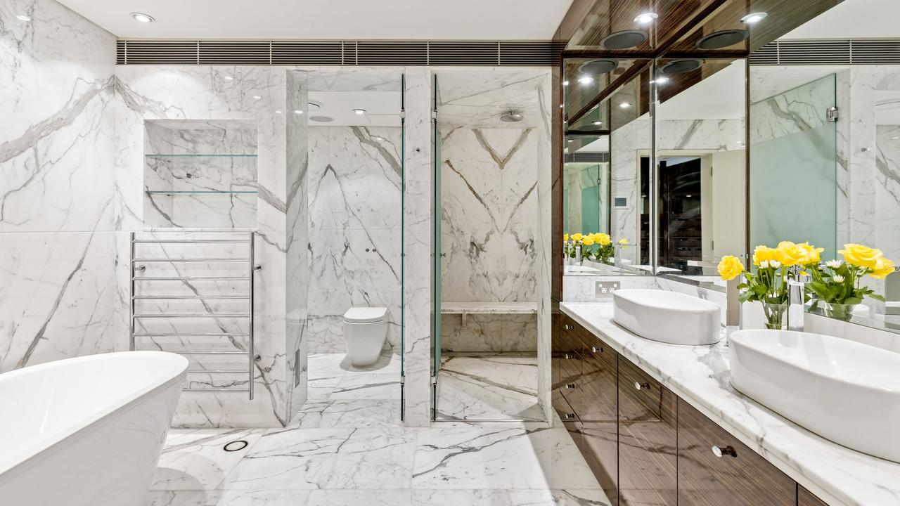 Book-matched marble are an impressive feature of the lavish bathrooms.