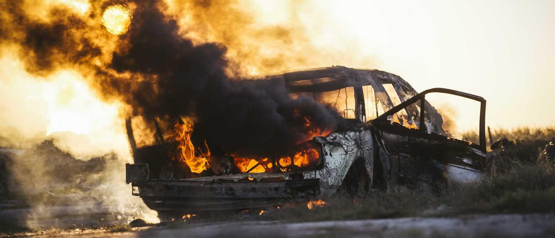 Burning car covered in black smoke
