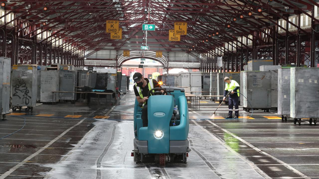 Workers are seen cleaning an empty Victoria Market which was declared a exposure site.